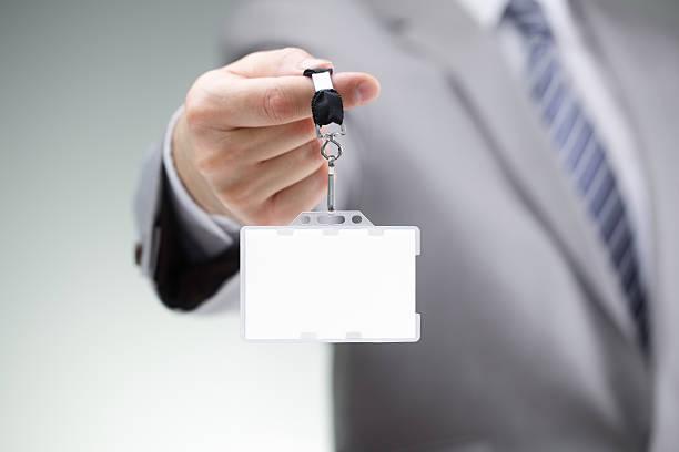 Businessman holding blank ID badge stock photo