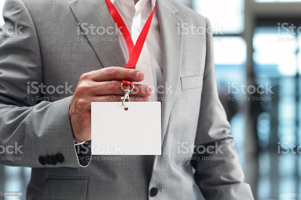Businessman holding blank ID badge stock photo