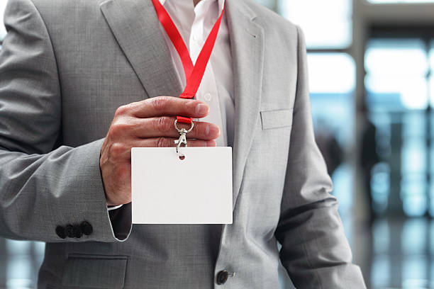 empresario sosteniendo en blanco de identificación de tarjeta - insignia símbolo fotografías e imágenes de stock