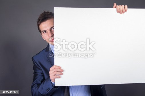 istock Businessman holding blank table for text 462749927