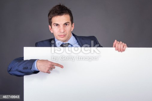 istock Businessman holding blank table for text 462749943