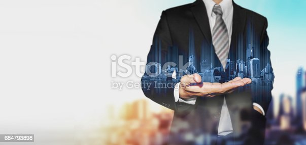 684793898 istock photo Businessman holding blue hologram of modern buildings, innovation technology concept 684793898