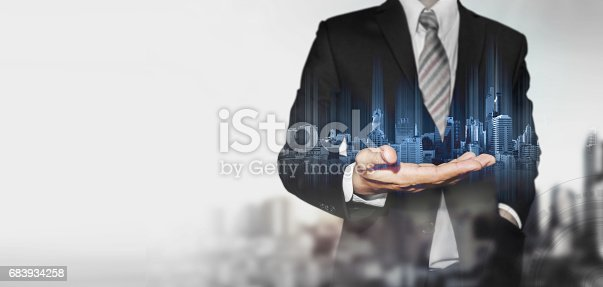 684793898 istock photo Businessman holding blue hologram of modern buildings, with blur background and copy space 683934258