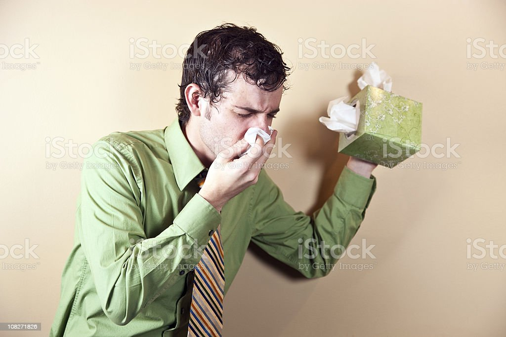 Businessman Holding Box of Tissues and Blowing Nose stock photo