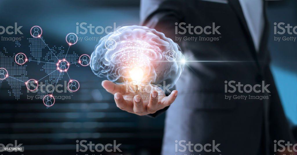 Businessman holding brain and light bulb with global networking connection, brainstorm and business concept stock photo