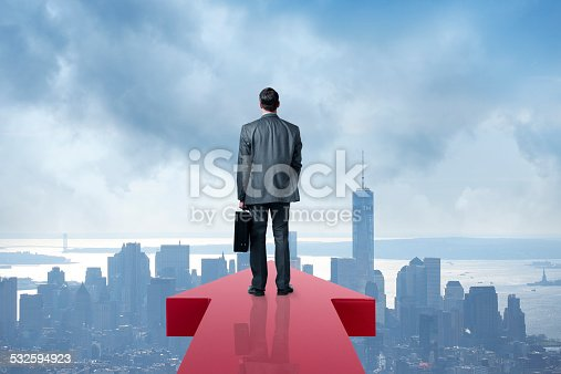 istock Businessman Holding Briefcase At The End Of An Arrow 532594923