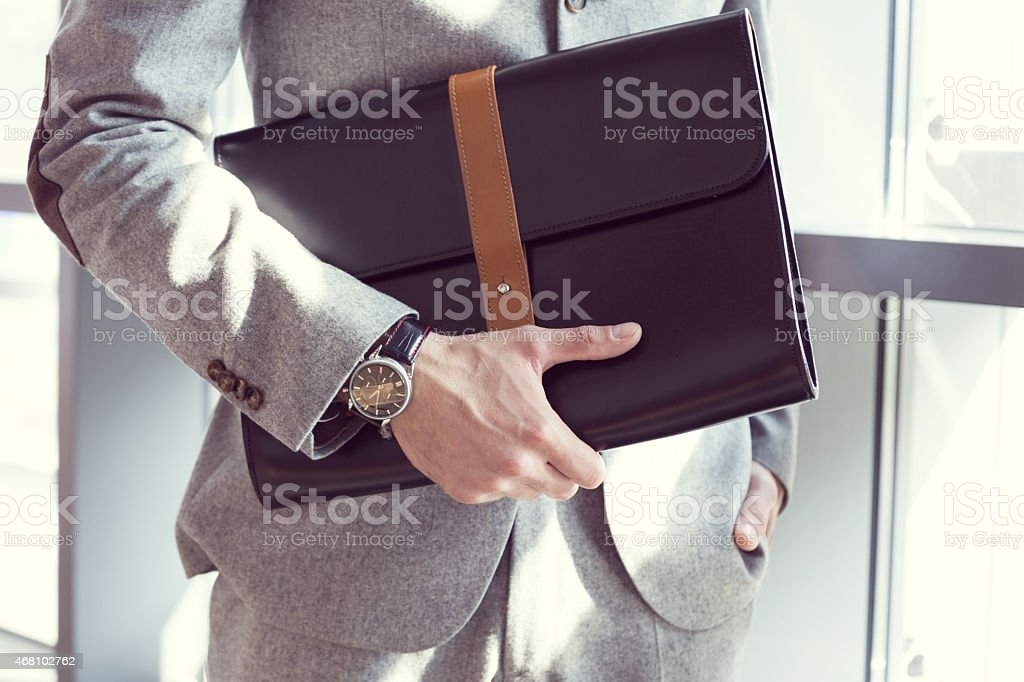 Businessman holding briefcase, close up stock photo