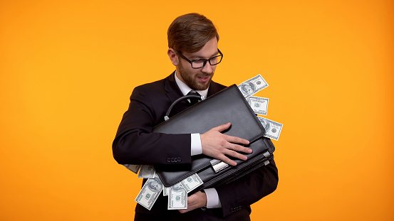 Businessman holding briefcase full of money, isolated on yellow background