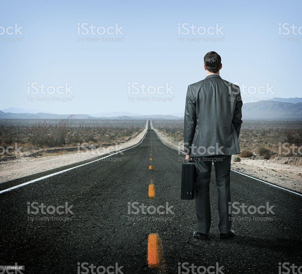 Businessman holding briefcase looking down long desert highway stock photo