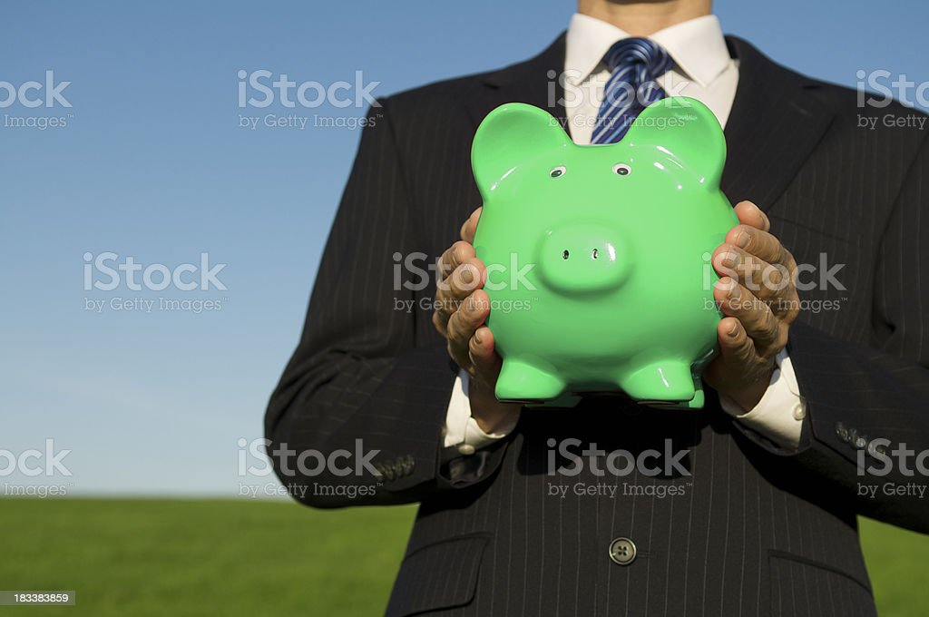 Businessman Holding Bright Green Piggy Bank in Field stock photo