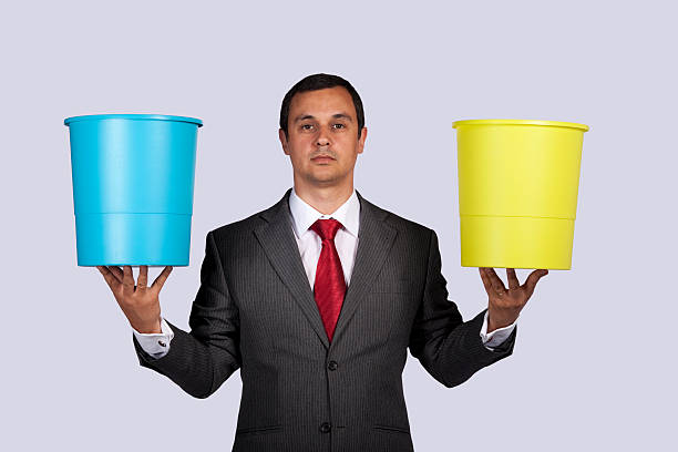 Businessman holding buckets stock photo