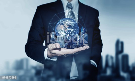 684793898 istock photo Businessman holding buildings with global network connection. Elements of this image are furnished by NASA 874673666