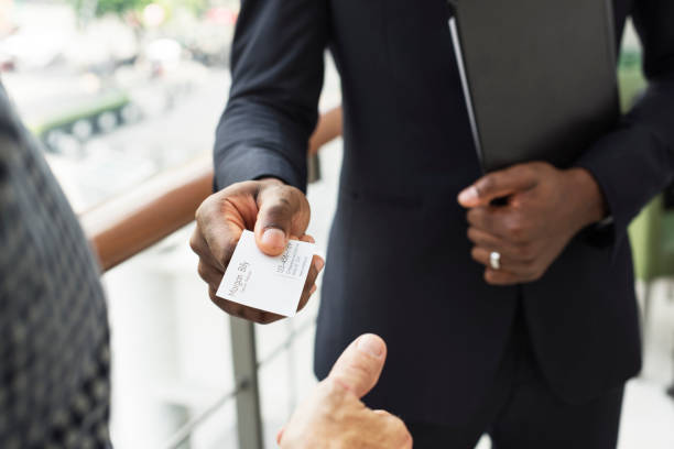 Businessman holding business card giving to another stock photo