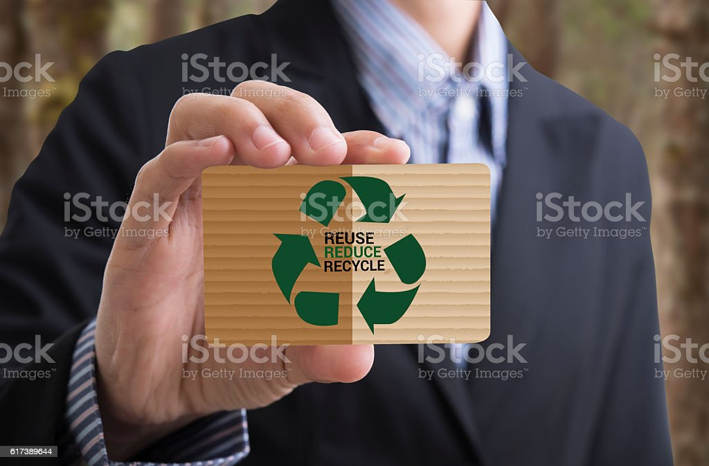 Businessman holding business card message recycle, reduce, reuse. stock photo