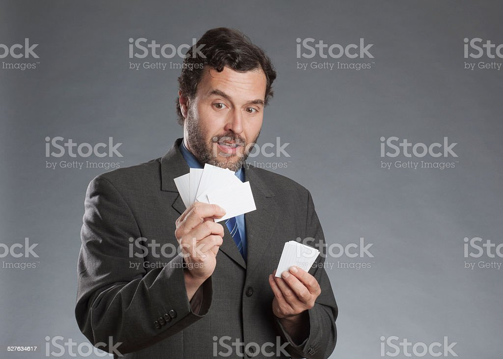 Businessman holding business cards against gray background stock photo