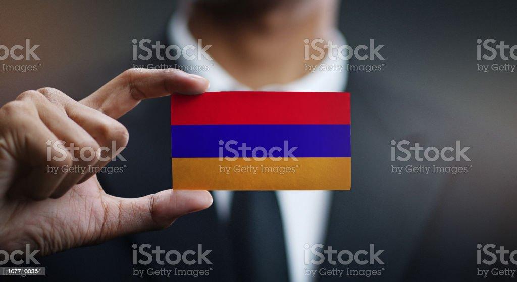 Businessman Holding Card of Armenia Flag stock photo