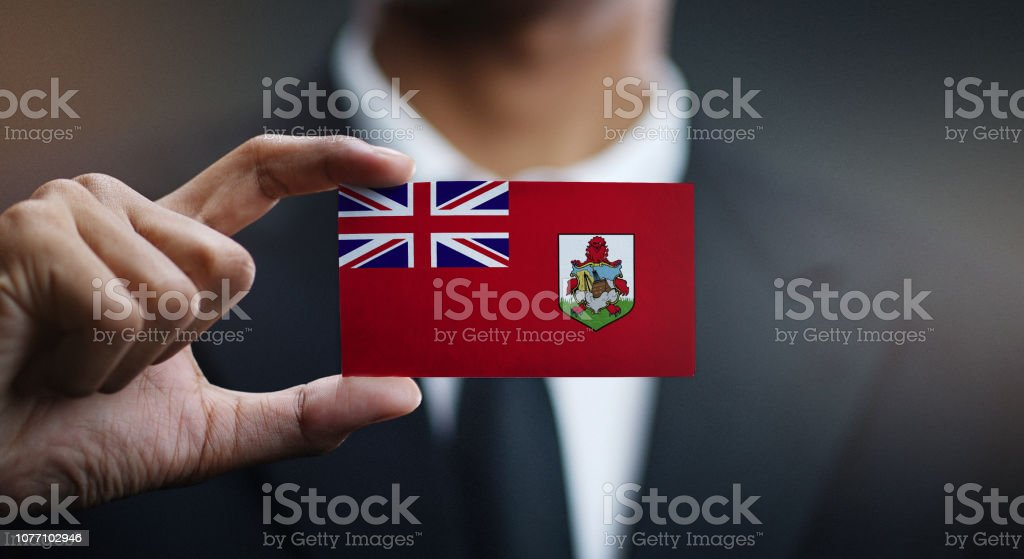 Businessman Holding Card of Bermuda Flag stock photo