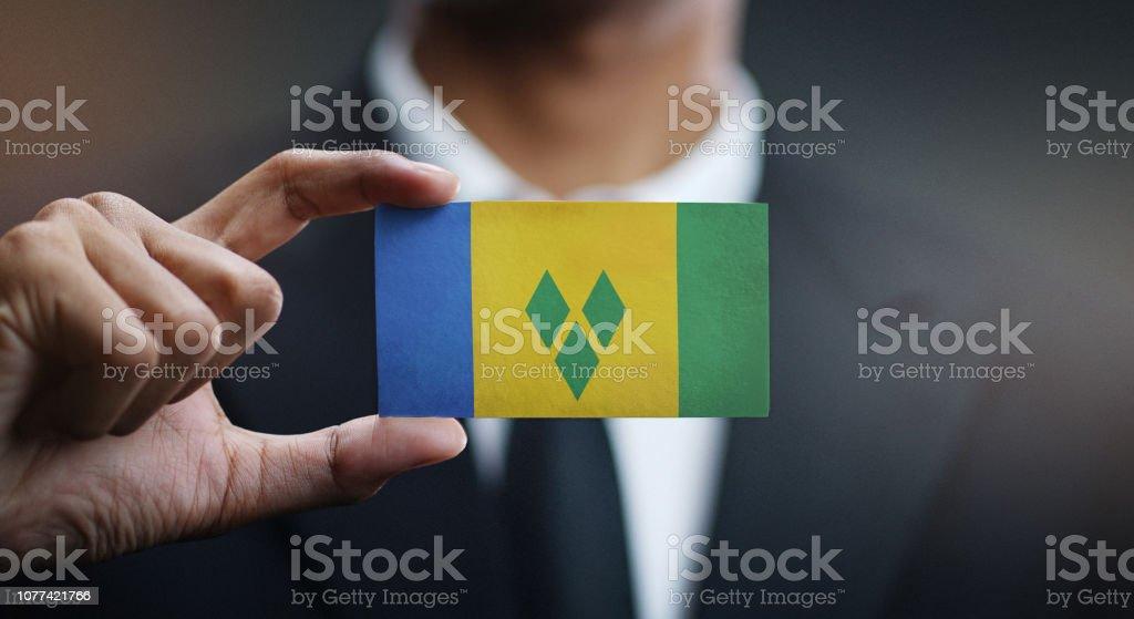 Empresário, segurando o cartão da bandeira de São Vicente e Granadinas - foto de acervo