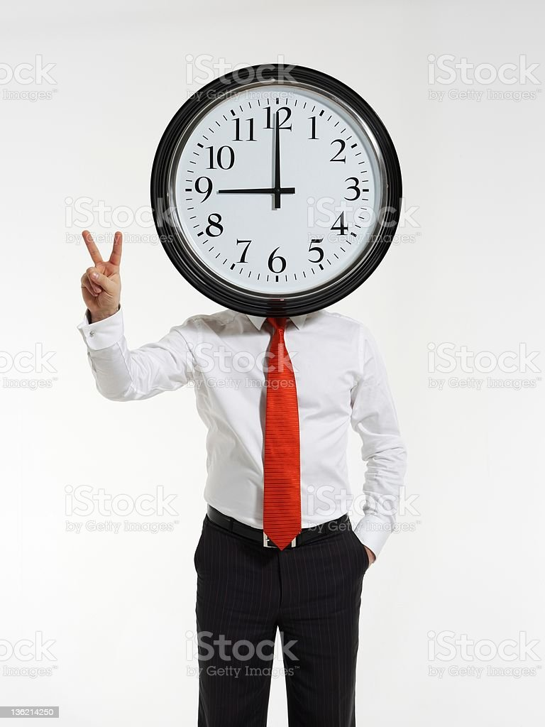 Businessman holding clock in front of his head royalty-free stock photo