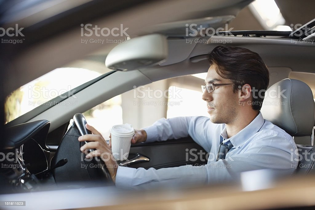 Businessman holding coffee cup and driving car stock photo