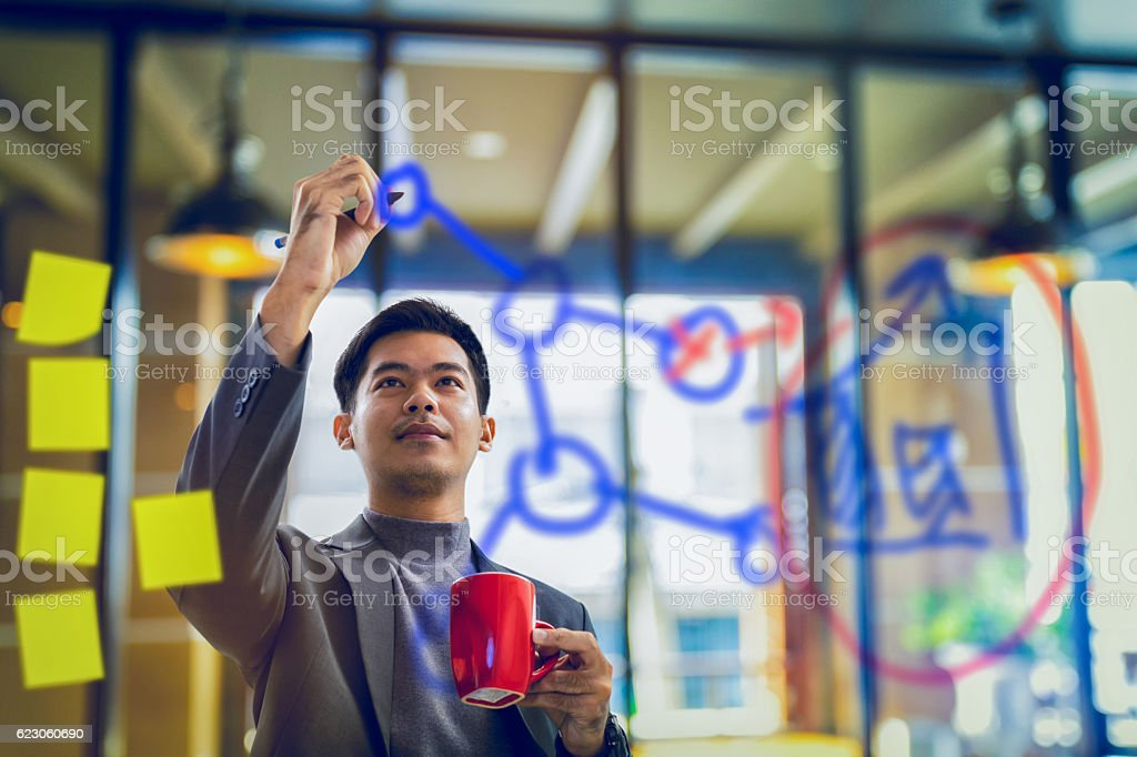 businessman holding coffee mug and writing data on transparent stock photo