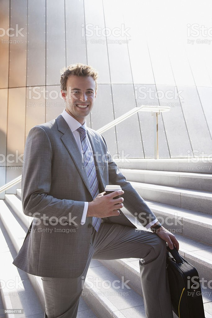 Businessman holding coffee on steps outdoors royalty-free stock photo