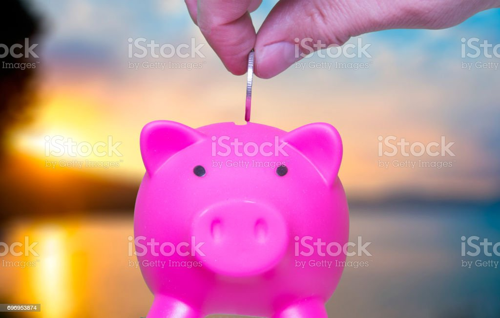 Businessman holding coin and pink piggy bank on sunset background selective and soft focus stock photo