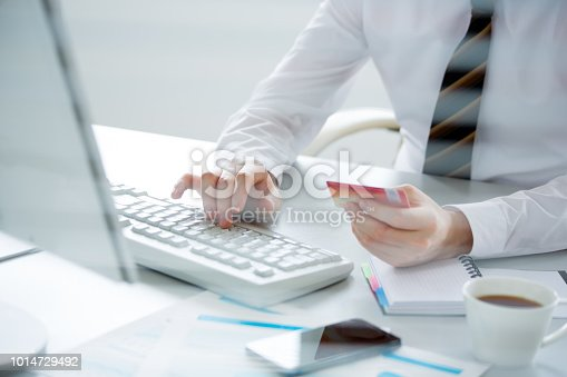 879813798 istock photo Businessman holding credit card and using laptop. 1014729492