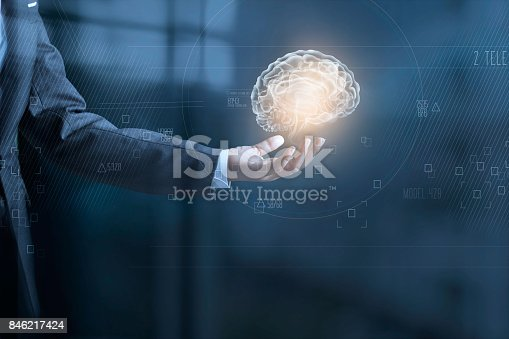 istock Businessman holding digital human brain and icon graphic in hand on dark blue background 846217424