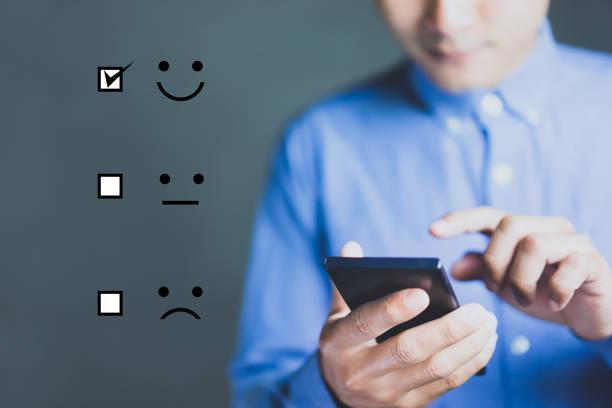 geschäftsmann hält digitales smartphone mit einem kontrollkästchen auf excellent smiley face rating für eine zufriedenheitsumfrage, customer experience concept. - feedback stock-fotos und bilder