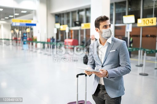 Businessman holding digital tablet at airport using protective mask