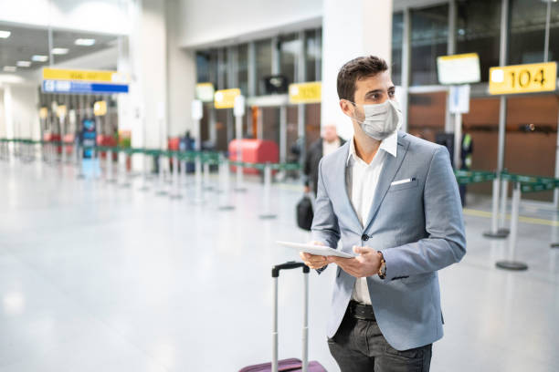 Businessman holding digital tablet at airport using protective mask stock photo
