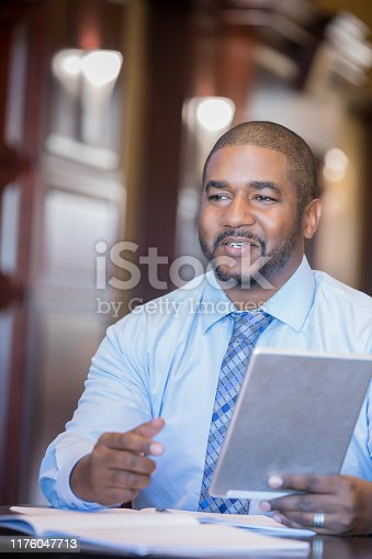 istock Businessman holding digital tablet at his desk 1176047713