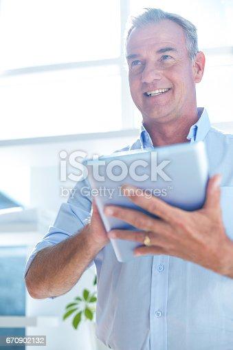 istock Businessman holding digital tablet at office 670902132