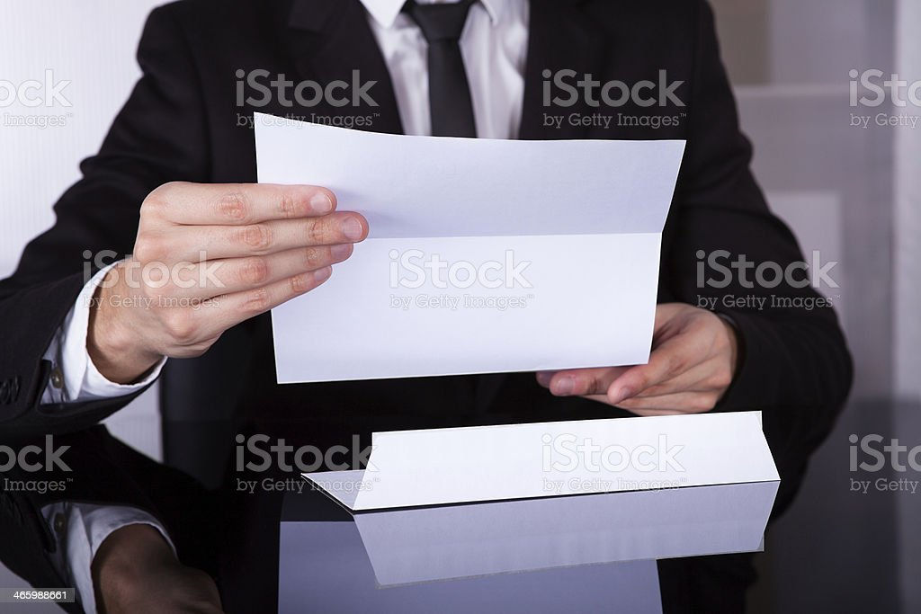 Businessman Holding Document At Desk stock photo