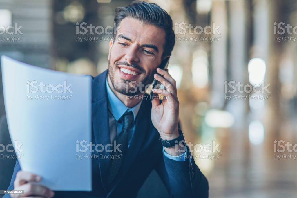 Businessman holding documents and talking on the phone stock photo