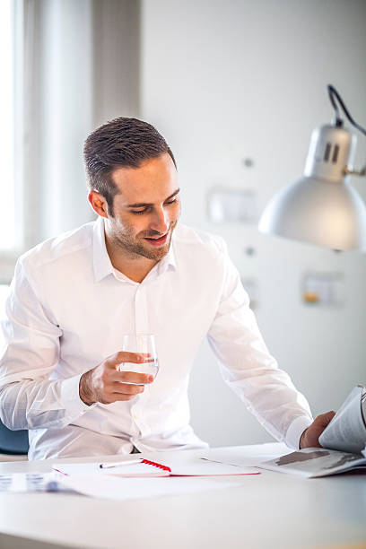 Businessman holding drinking glass while reading brochure in office – Foto