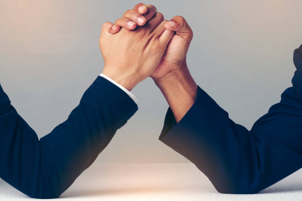 Businessman Holding Each Other Hands Over Desk, arm wrestling over stock photo