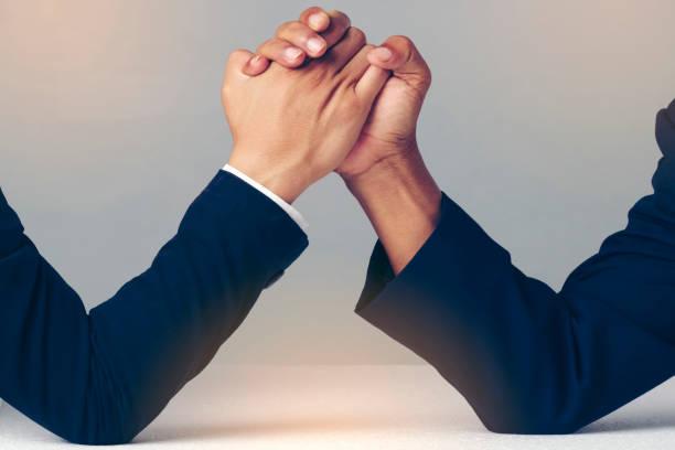 empresario sosteniendo mutuamente las manos sobre escritorio, vencidas en - duelo fotografías e imágenes de stock