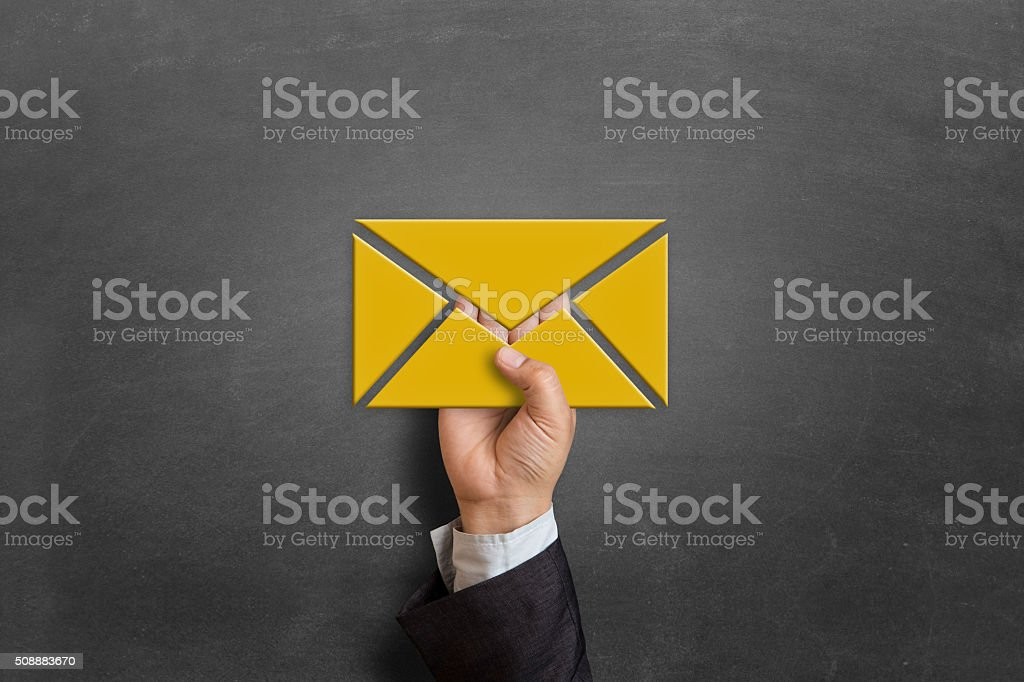 Businessman holding E-mail icon on blackboard stock photo