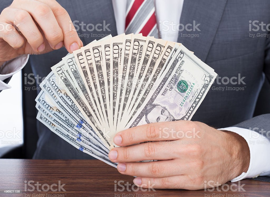 Businessman Holding Fanned Banknotes stock photo