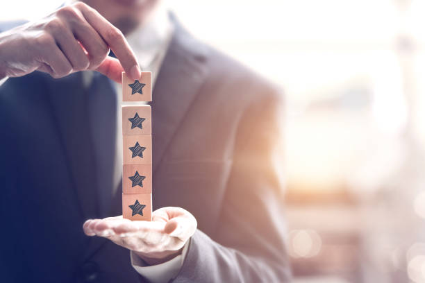 Businessman holding five star symbol to increase rating of company stock photo