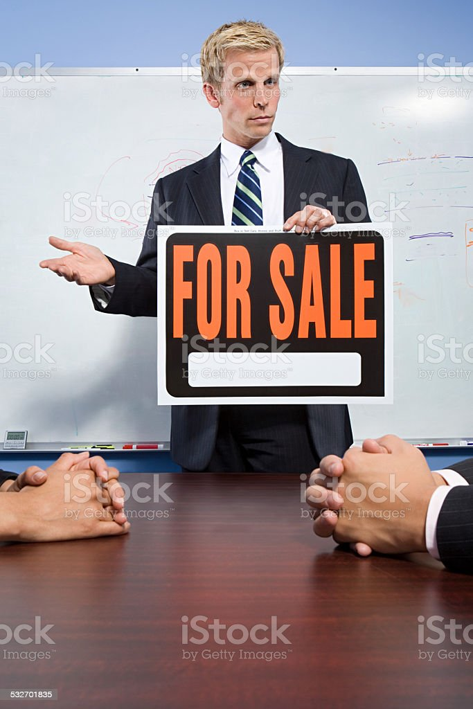 Businessman holding for sale sign stock photo