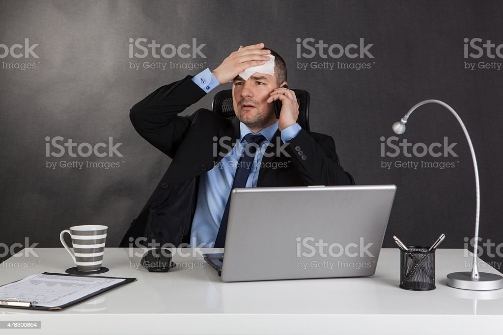 Businessman holding forehead in office. stock photo