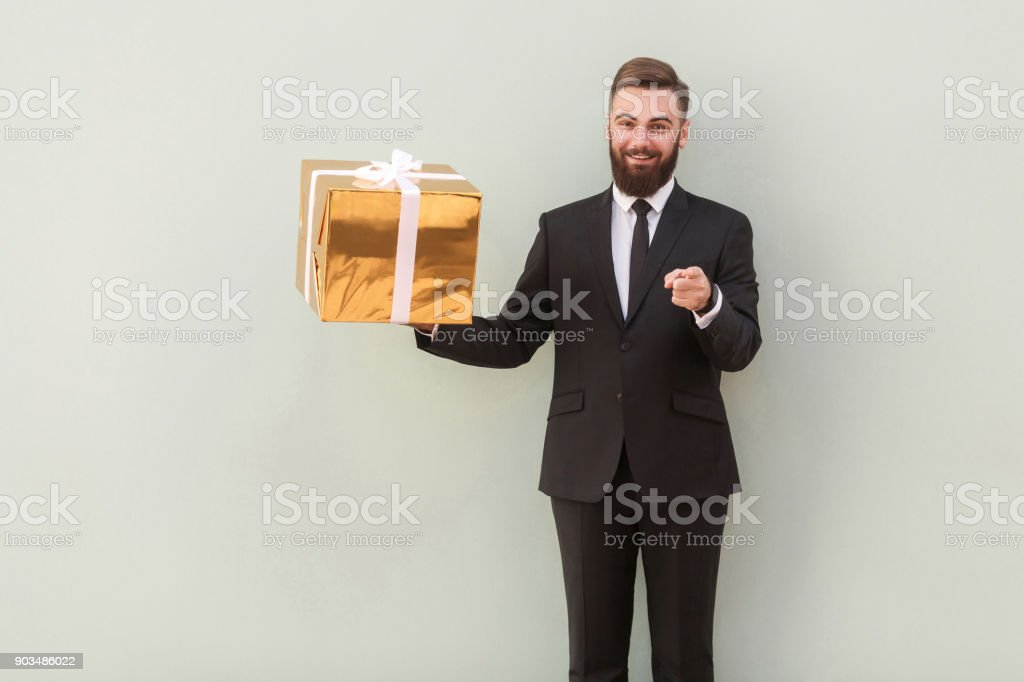 Businessman holding gift box, pointing fingers at camera and smiling stock photo