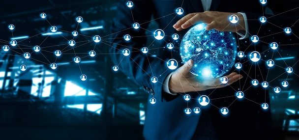 istock Businessman holding global customer network connection in hands.Technology  and structure networking and data exchanges communication on dark blue background. Elements of this image furnished by NASA. 1025744810