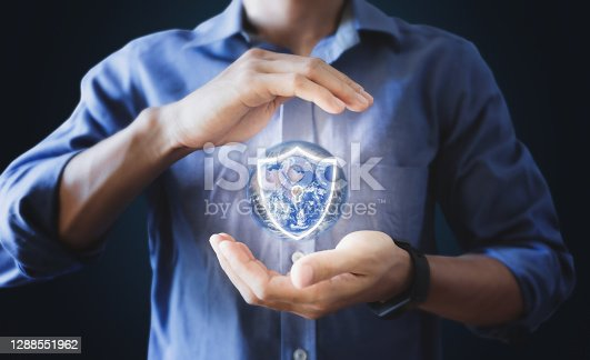 Businessman holding globe with protection shield icon. Saving earth, Energy saving and Security concept. Element of this image are furnished by NASA