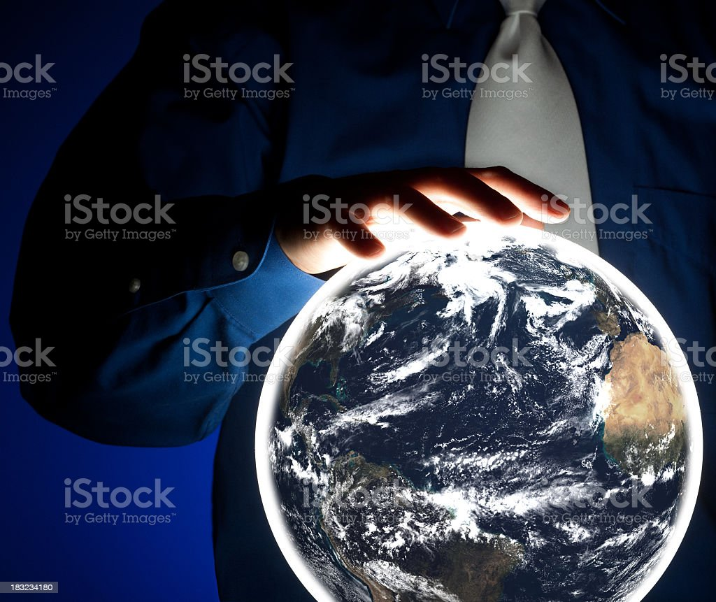 Businessman holding glowing crystal ball with image of planet earth royalty-free stock photo
