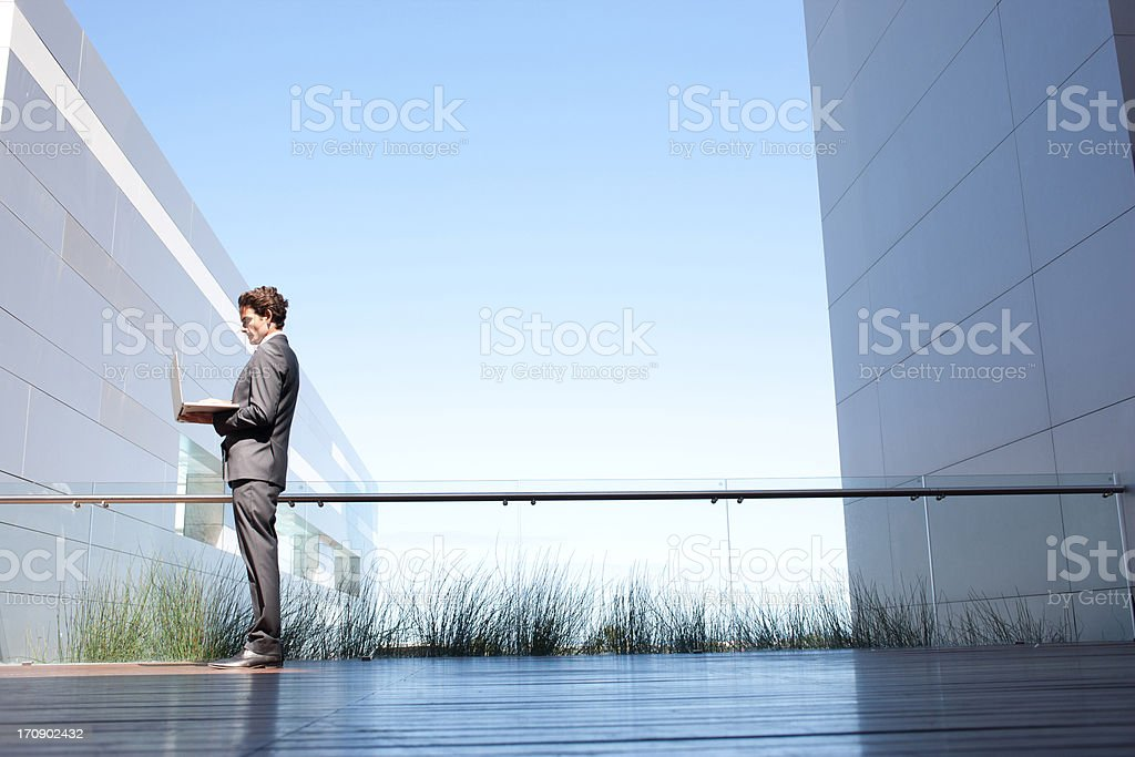 Businessman holding glowing laptop on balcony royalty-free stock photo