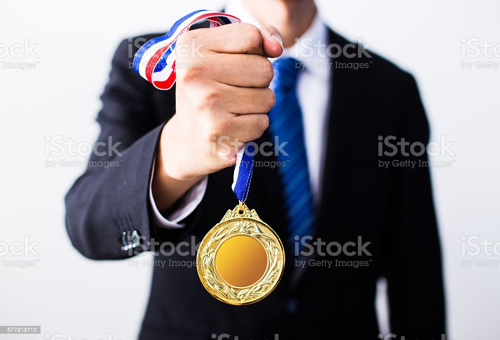businessman holding gold medals stock photo